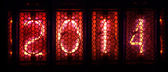 Year 2014 shown by numerical vacuum tubes, also known as Nixie tubes. Pink glowing numbers on black background. — Stock fotografie