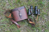 An old pair of binoculars with the cover on the grass — Stock Photo