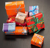 Colourful gift boxes of different sizes, black background — Stock Photo