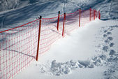 Footprints on the snow slope with the protective screen — Stockfoto