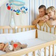 Happy parents near baby's bed — Stock Photo