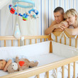 Happy parents near baby's bed — ストック写真