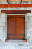 Wooden window in the stone wall — Stock Photo