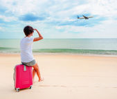 Woman with a suitcase on the beach — Stock Photo
