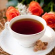 Stock Photo: Cup of teand brown sugar and roses