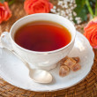Stock Photo: Cup of teand brown sugar and flowers roses