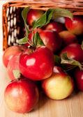 Masanın üzerinde bir sepet içinde kırmızı elmalar — Stok fotoğraf