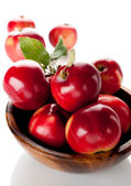 Red apples in a wooden bowl — Stock Photo