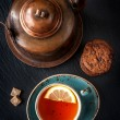 Vintage copper kettle on a slate board and tea with chocolate cookies — Stock Photo #32511217