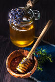 Pot of honey with lavender and a spoon for honey on a wooden background — Stock Photo