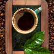 Stock Photo: Cup of espresso coffee with green leaves on chalkboard on background of coffee beans