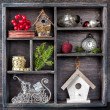 Christmas decorations set: antique clocks, birdhouse, Santa's sleigh and Christmas toys in an old wooden box — Stock Photo #33594601