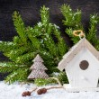 Сhristmas tree decoration and birdhouse on wooden background — Stock Photo #34567189