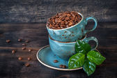 Roasted coffee beans with green leaves in cups — Foto Stock