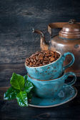 Roasted coffee beans with green leaves in cups and vintage pot — Stock Photo