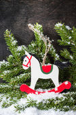 Christmas rocking horse and spruce branches with snow. — Stock Photo