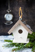 Сhristmas tree decoration, antique clock and birdhouse on a wooden background — Stock Photo