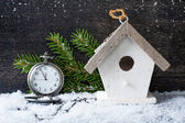 Christmas antique clock and a birdhouse on a wooden background — Stock Photo
