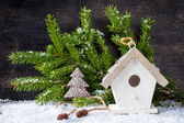 Сhristmas tree decoration and birdhouse on a wooden background — Stock fotografie