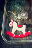 Christmas tree toy rocking horse and antique clock — Stock Photo