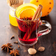 Hot Christmas drink (mulled wine) with spices, honey and orange — Stock Photo