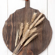 Wheat ears on vintage board — Stock Photo