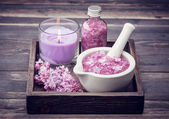 Sea salt, candle and lilac flowers. — Stock Photo