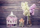 Bouquet lilac flowers, angel and bird cage — Photo