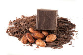 Chocolate cube, grated chocolate and cocoa beans — Stock Photo