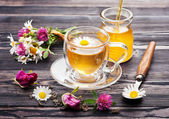 Herbal tea with honey and flowers. Chamomile tea, tea with rose petals and flowers clover. — Stock Photo