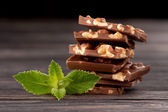 Chocolate with nuts and mint on dark wooden background — 图库照片