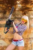 Sexig tjej håller en motorsåg — Stockfoto