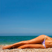 A woman sunbathes on a beach — Stok fotoğraf
