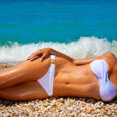 A woman sunbathes on a beach — Stock Photo