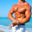 Muscular brutal man on the beach — Stock Photo