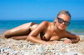 Een vrouw sunbathes op een strand — Stockfoto