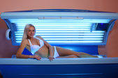Woman sunbathing in the solarium — Stock Photo