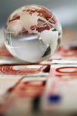 A globe and cash money closeup. — Stock Photo