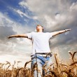Happy man standing with open arms on a wheat field — Stock Photo #14058821
