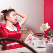 Young smiling woman in red dress sitting at cafe — Stock Photo