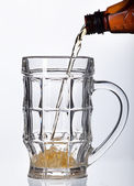 Beer pouring into beer mug isolated on white — Stock Photo