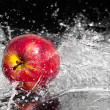 Fresh an apple in streaming splash water on black background - Stock Photo