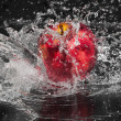 Fresh an apple in streaming splash water on black background — Stock Photo