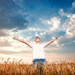 Happy man standing with open arms on a wheat field — Stock Photo