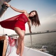 Pretty young woman in red dress posing on the yacht — Stock Photo