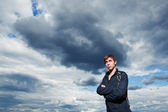 Young handsome muscular man in a nature and clouds — Stock Photo