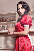 Beautiful young woman in red dress in restaurant — Stock Photo
