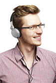 Listens and smiles with headphones — Stock Photo
