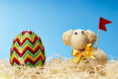 Easter egg and easter lamb in hay — Zdjęcie stockowe