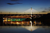 Highlighted bridge at night and reflected in the water — Stock Photo